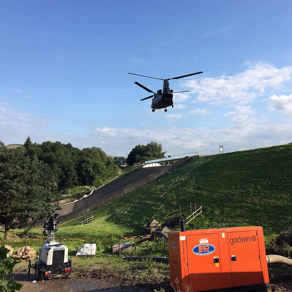 An RAF Chinook flies over one of SLD's hire units on site